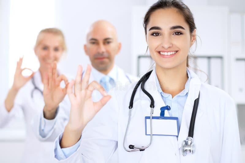 Donna felice di medico con il personale medico all'ospedale I pollici aumentano e segno giusto fotografia stock libera da diritti