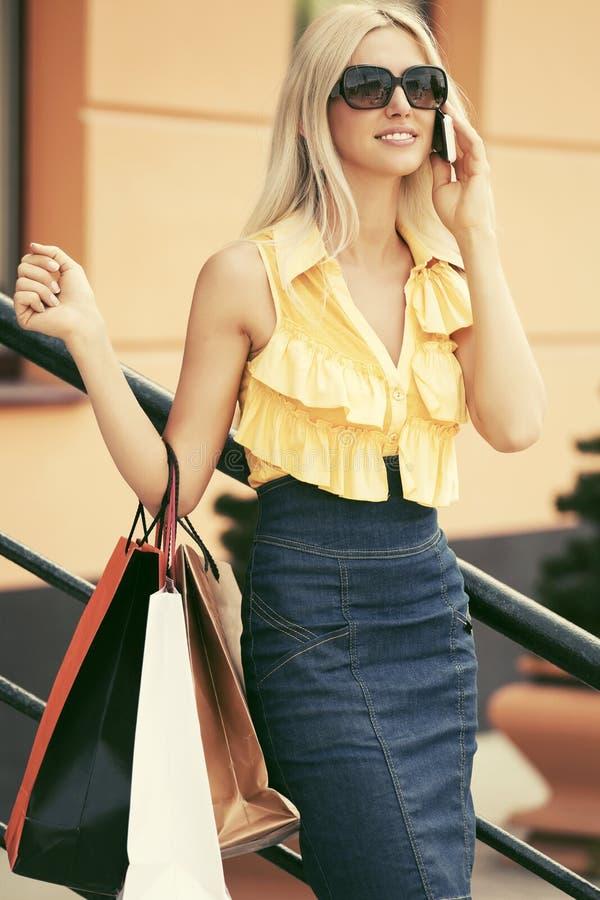 Donna felice di modo con i sacchetti della spesa che parla sul telefono cellulare al centro commerciale fotografia stock