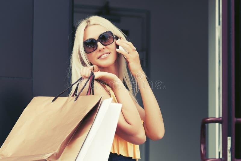 Donna felice di modo con i sacchetti della spesa che rivolge al telefono cellulare immagine stock libera da diritti