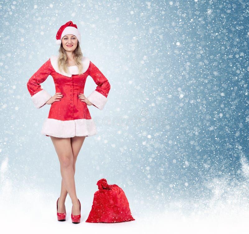 Donna felice di Santa con la grande borsa rossa piena dei regali, su fondo e su neve blu immagine stock