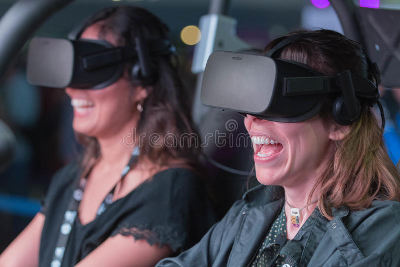 Donna felice di sorriso che ottiene esperienza facendo uso dei vetri della cuffia avricolare di VR fotografia stock libera da diritti