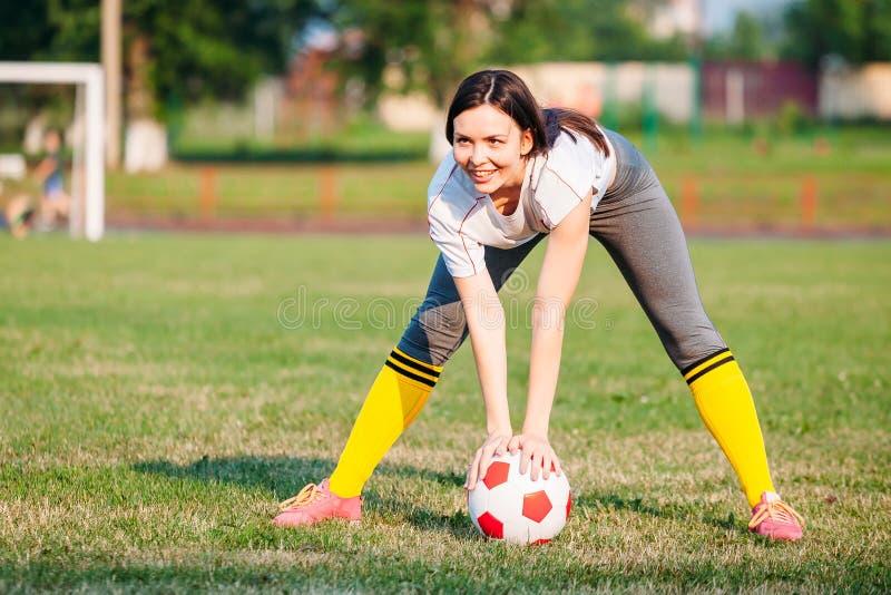 Donna felice di sorriso con pallone da calcio sul campo da calcio tenendo nella palla di mani fotografie stock libere da diritti