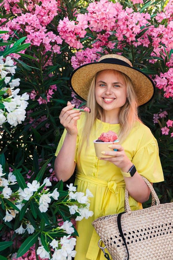 Donna felice di sorriso mangiare e godere del gelato fotografia stock