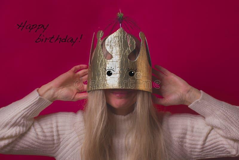 Donna felice divertente in corona del cartone dell'oro sui precedenti rosa fotografia stock