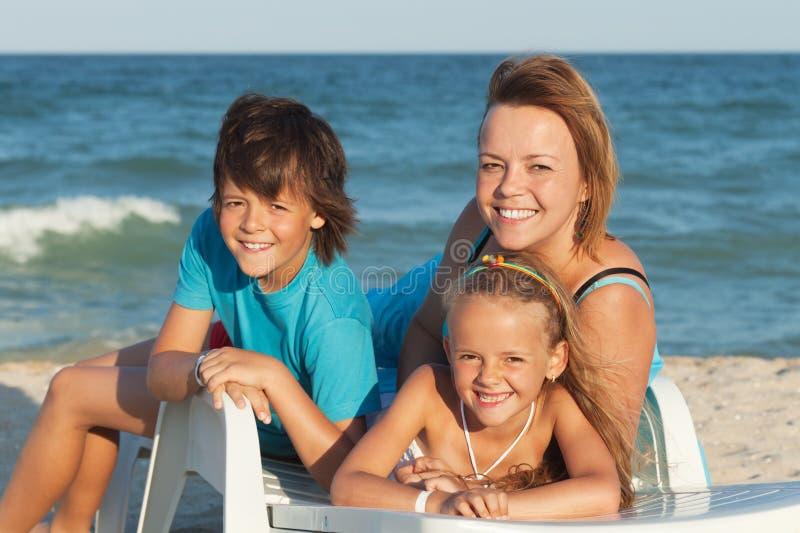 Donna felice e bambini che si rilassano su uno sdraio dal mare fotografia stock