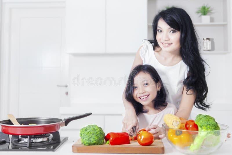 Donna felice e bambino che cucinano nella cucina immagini stock
