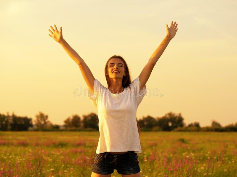 Donna felice e serena di comportamento all'aperto con le mani sollevate fotografia stock libera da diritti