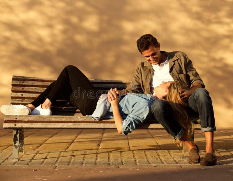 Donna felice ed uomo dell'ente completo nell'abbraccio sul banco di parco immagine stock