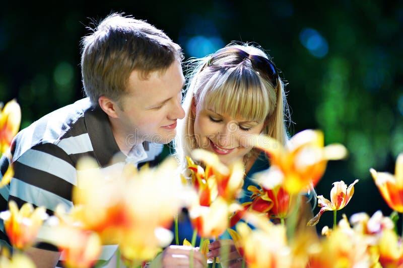 Donna felice ed uomo elegante fra i fiori fotografia stock