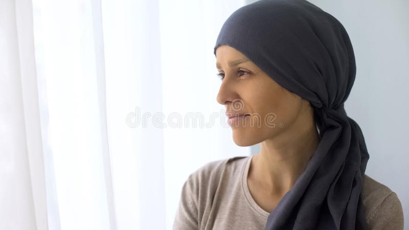 Donna felice in foulard che guarda nella finestra, recupero dopo trattamento del cancro fotografia stock