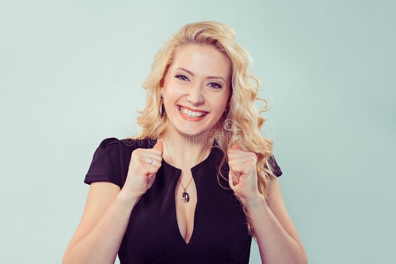Donna felice incantante che tiene i pugni nel supporto fotografie stock libere da diritti