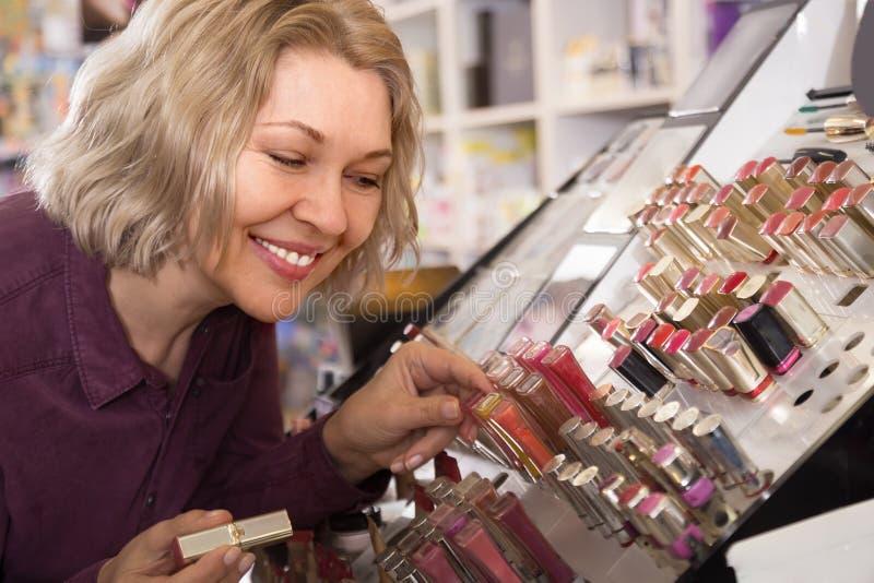 Donna felice matura che sceglie labbro più grassoccio su esposizione fotografia stock libera da diritti
