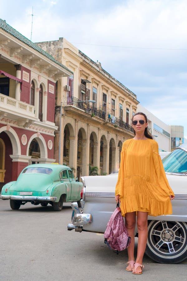 Donna felice nell'area popolare a vecchia Avana, Cuba Automobili variopinte sorridenti del fondo felice del giovane girltraveler fotografie stock libere da diritti