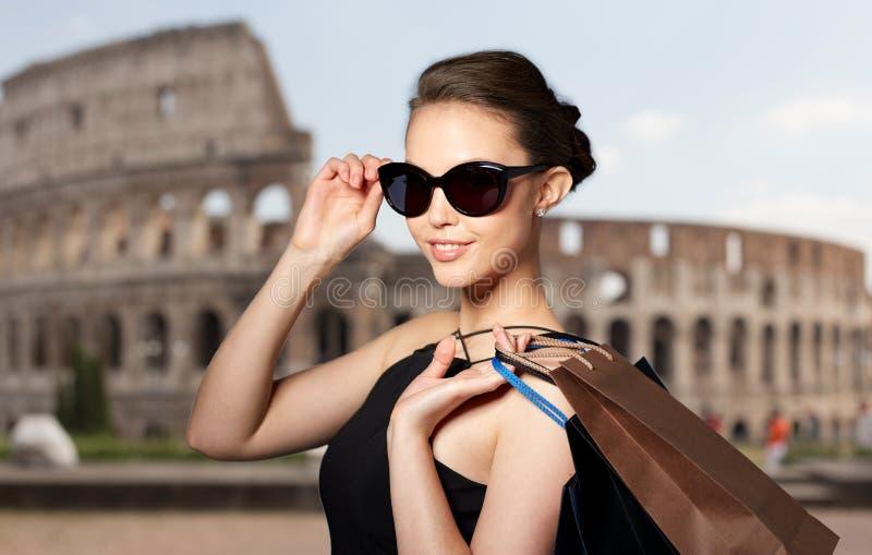 Donna felice in occhiali da sole neri con i sacchetti della spesa fotografie stock