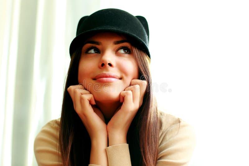 Donna felice premurosa nel distogliere lo sguardo sveglio del cappello fotografia stock libera da diritti