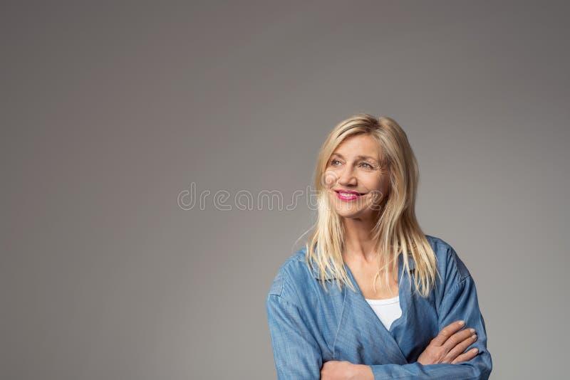 Donna felice premurosa su Gray con lo spazio della copia fotografie stock