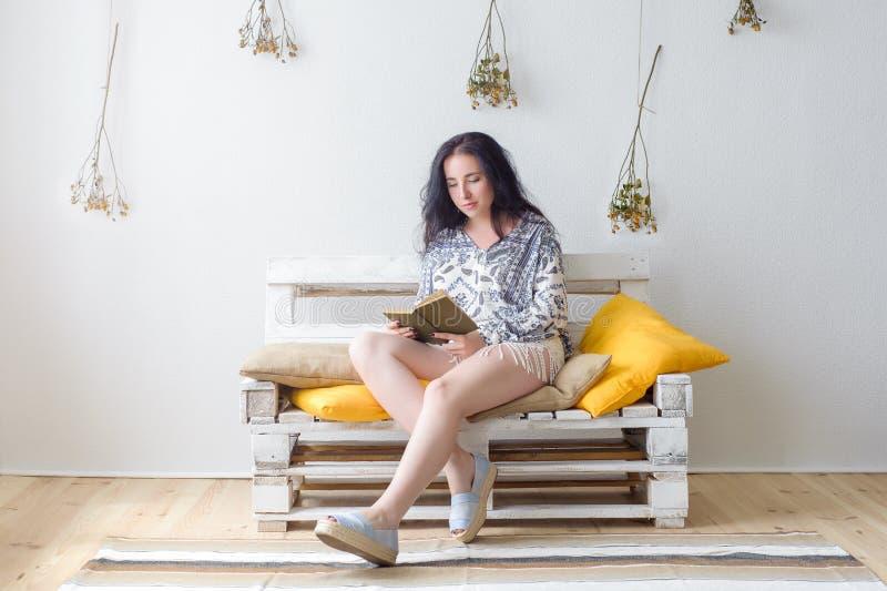 Donna felice rilassata che legge un libro che si siede su uno strato a casa fotografie stock