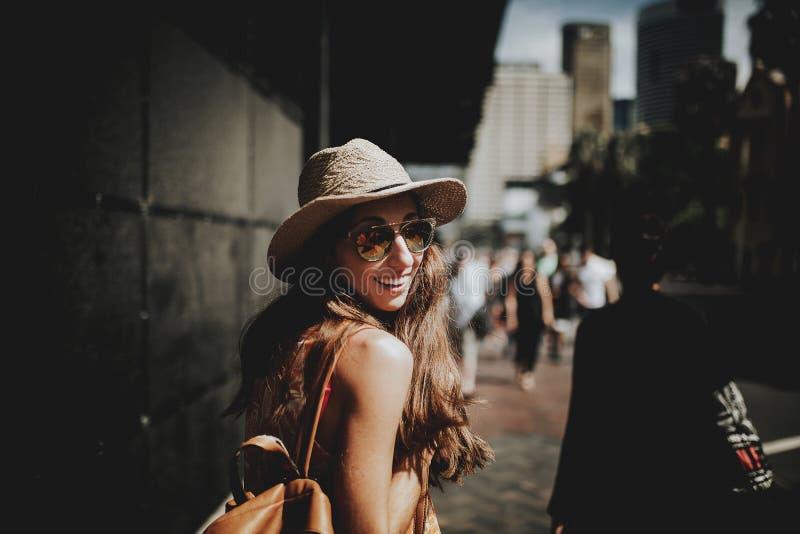 Donna felice sorridente che cammina in una via di Sydney e che gira intorno per esaminare la macchina fotografica immagini stock