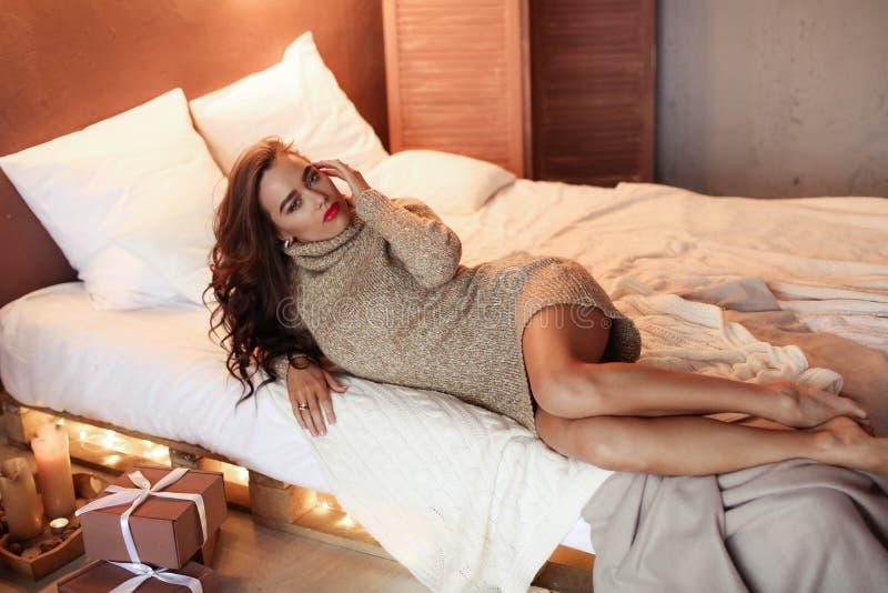 Donna felice sorridente con il contenitore di regalo che si trova a letto ed esaminare macchina fotografica fotografie stock libere da diritti