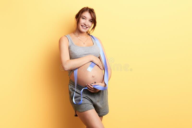 Donna felice sorridente con un nastro sulle sue spalle che esaminano la macchina fotografica immagine stock