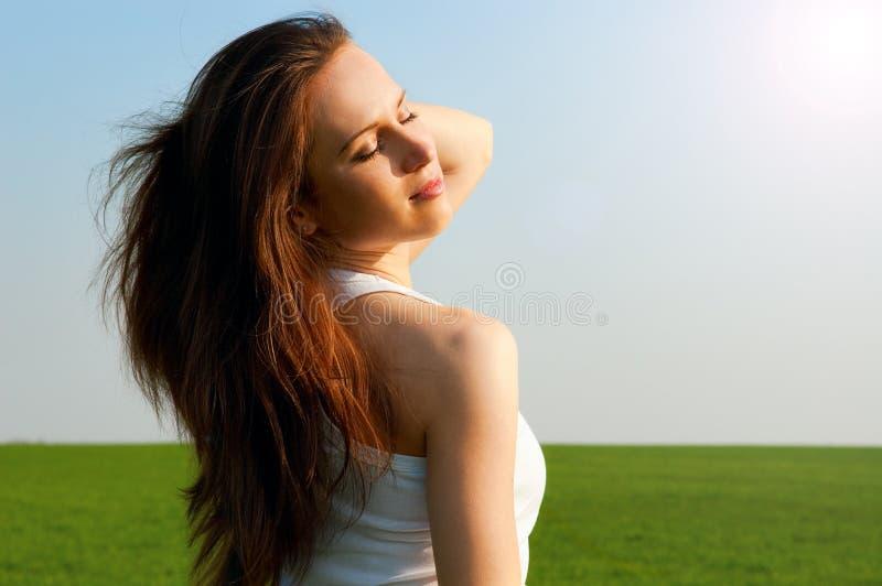 Donna felice sotto il sole della sorgente immagini stock