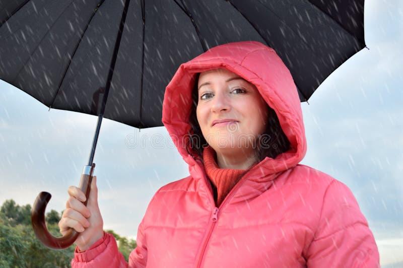 Donna felice sotto la pioggia immagine stock