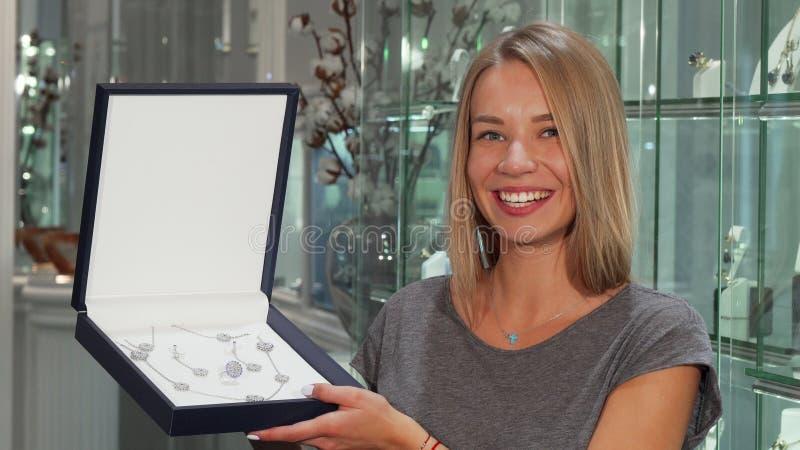 Donna felice splendida che sorride alla macchina fotografica che tiene l'insieme costoso dei gioielli fotografia stock libera da diritti