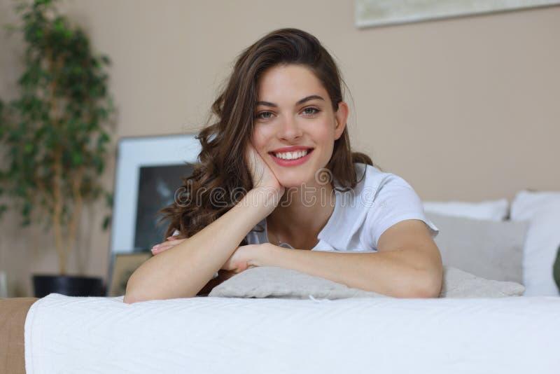 Donna felice sul letto che sorride e che allunga esaminando macchina fotografica fotografie stock libere da diritti