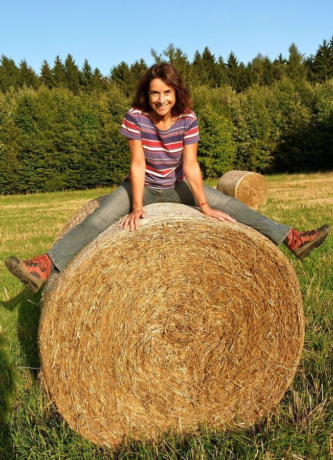 Donna felice sulla balla della paglia immagine stock