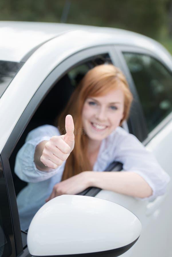 Donna felice in un nuovo dare dell'automobile pollici su fotografia stock