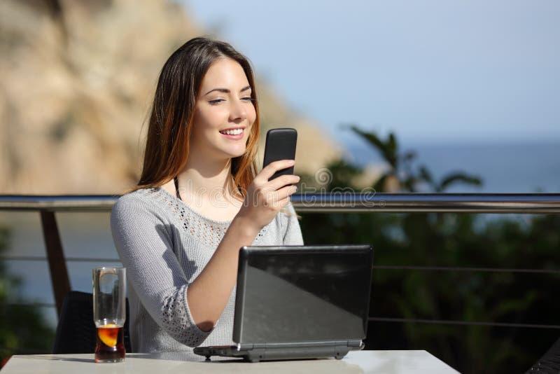 Donna felice in un ristorante con un computer e sul telefono fotografia stock