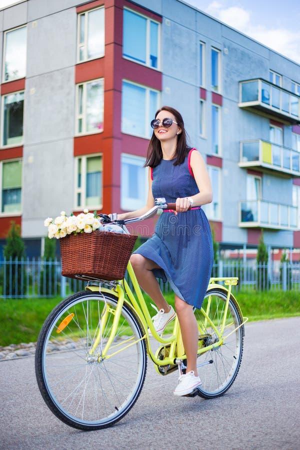 Donna felice in vestito che guida una bici immagine stock libera da diritti