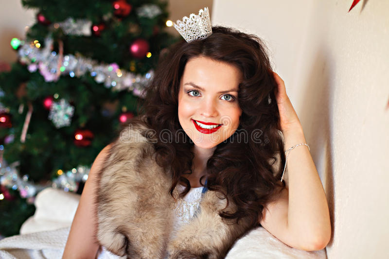 Donna felice in vestito festivo davanti all'albero di Natale immagine stock