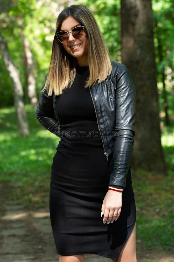 Donna felice in vestito nero e bomber ed occhiali da sole che posano in natura un giorno di molla soleggiato con la mano sull'anc fotografia stock