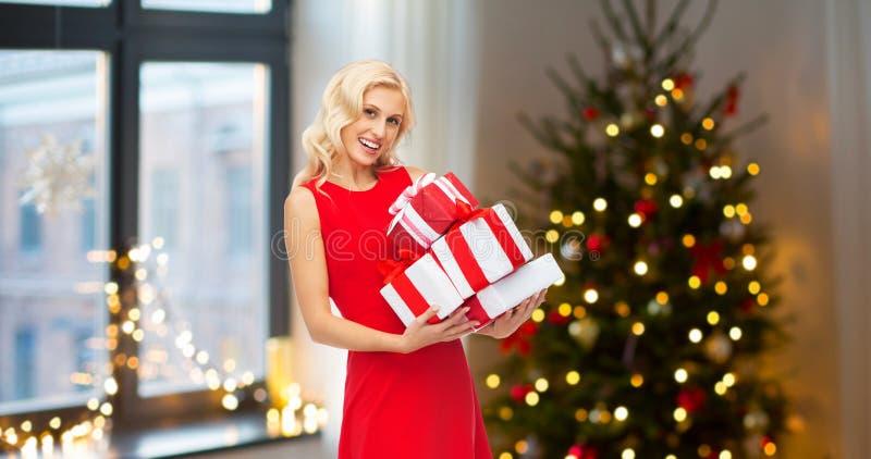 Donna felice in vestito rosso con i regali di natale fotografie stock libere da diritti