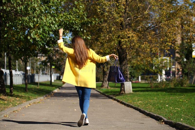 Donna felice in via di camminata di autunno del cappotto giallo fotografie stock libere da diritti