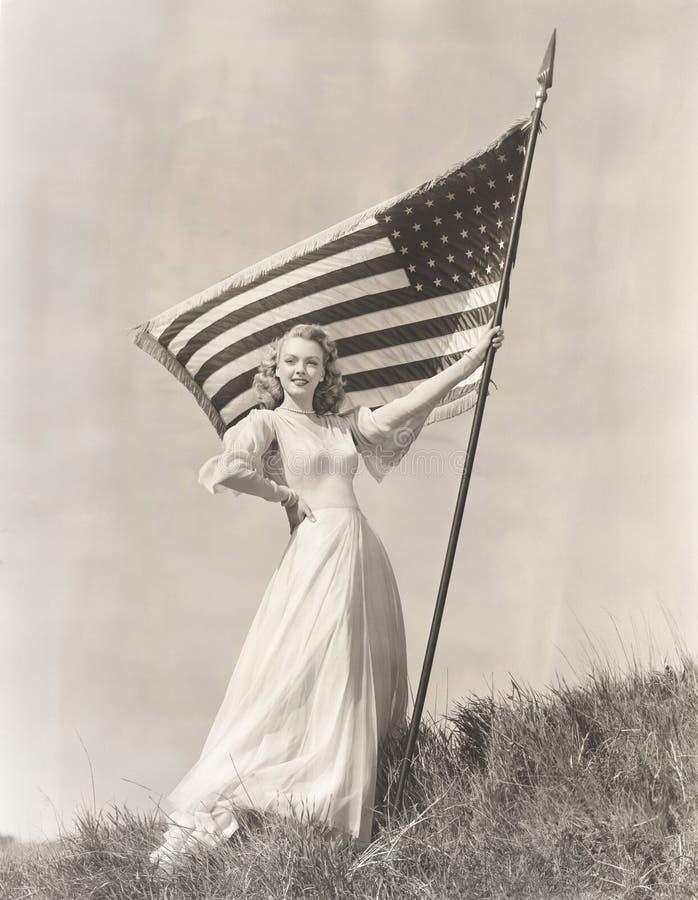 Donna fiera in bandiera americana della tenuta dell'abito sulla collina immagini stock