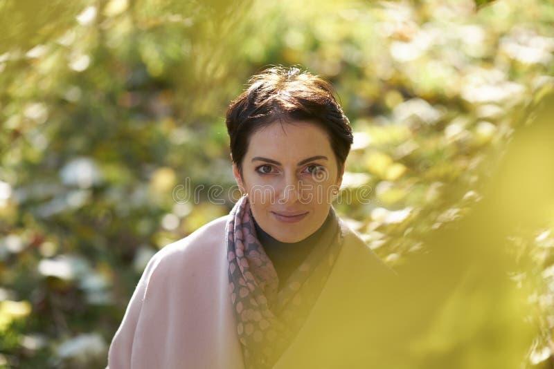 Donna in foglie di giallo di autunno fotografia stock