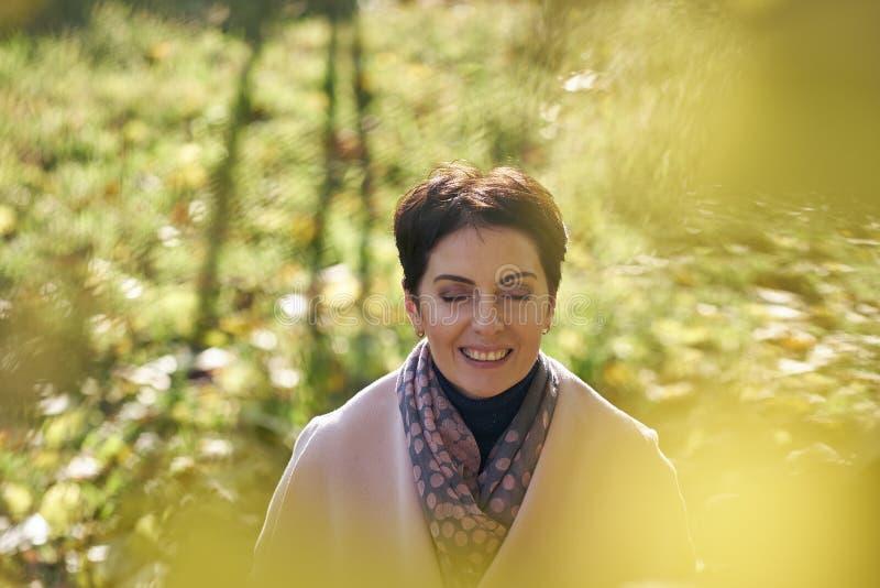 Donna in foglie di giallo di autunno fotografia stock libera da diritti