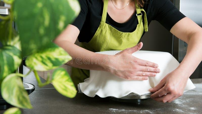 donna in forno che decora dolce con glassa reale fotografia stock libera da diritti