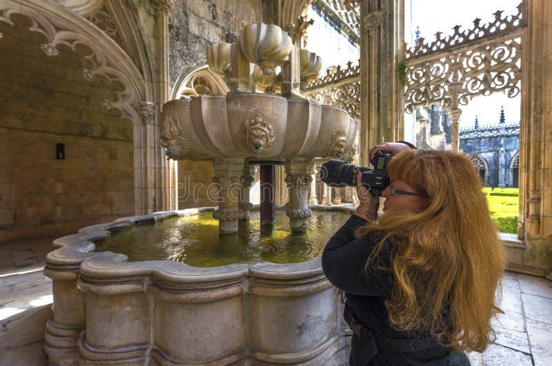 Donna-fotografo nel cortile del monastero di Batalha immagini stock