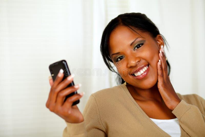 Donna fresca che tiene un mobile e che osserva a voi fotografia stock