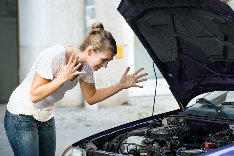 Donna frustrata che esamina il motore di automobile ripartito fotografia stock