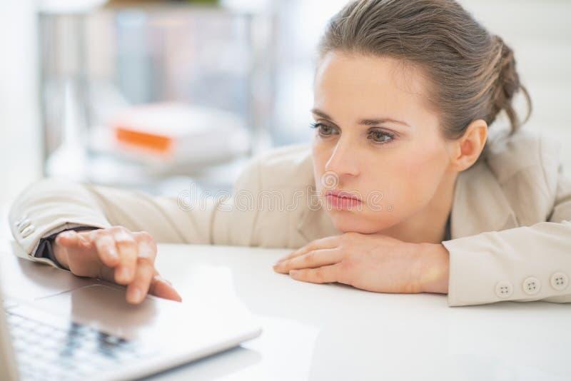 Donna frustrata di affari che lavora con il computer portatile fotografie stock