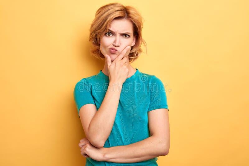 Donna frustrata infelice aggrottante le sopracciglia con una palma sul suo mento fotografie stock libere da diritti