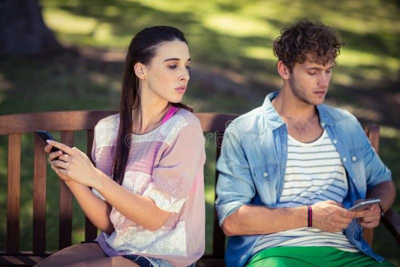 Donna gelosa che spia il telefono cellulare del suo uomo in parco fotografie stock libere da diritti