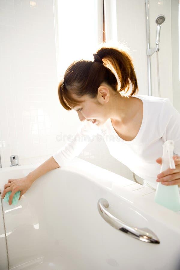 Donna giapponese che pulisce la vasca da bagno immagini stock