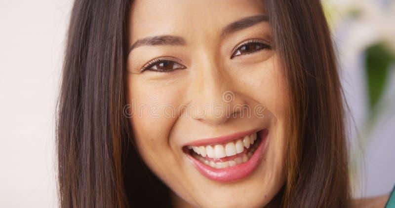Donna giapponese che sorride e che esamina macchina fotografica immagine stock