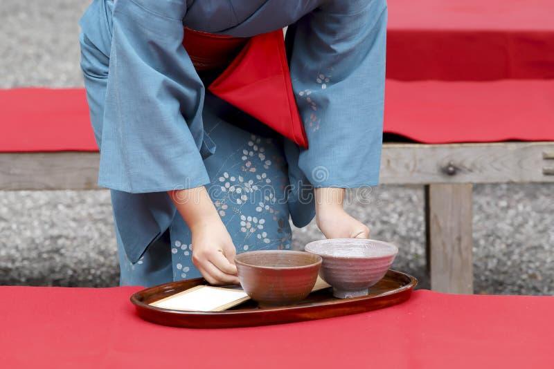 Donna giapponese nel tè verde del servizio del kimono immagine stock