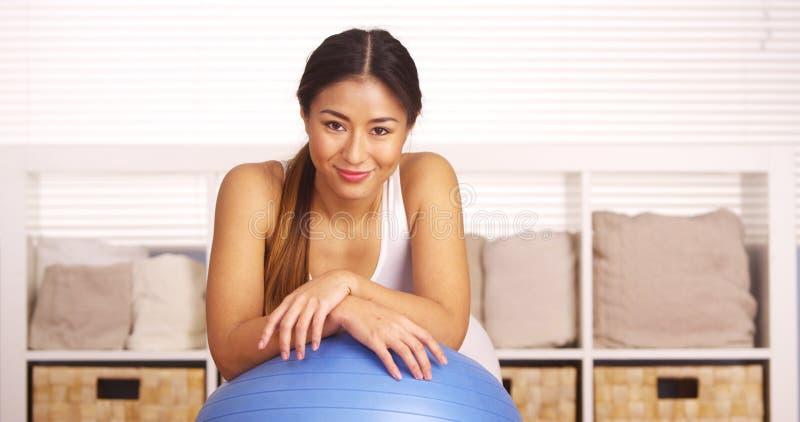 Donna giapponese sorridente che riposa sulla palla di allenamento immagini stock libere da diritti